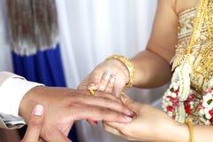 婚姻泰国结婚戒指,新娘在新郎,新娘上在新郎、泰国婚礼和婚礼把结婚戒指放投入了圆环 库存照片