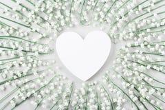 婚姻的大模型的白色心脏和铃兰花 美好的花卉模式 平的位置样式 免版税库存图片