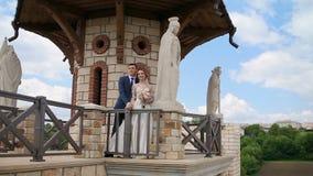 婚姻的夫妇通过与壮观的石雕象的一座古老石城堡走 影视素材