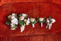 婚姻的套白玫瑰五朵钮扣眼上插的花在红色背景的 库存照片