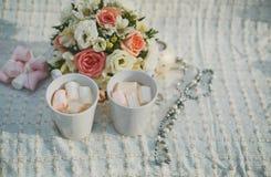 婚姻的摄影 婚姻的细节冬天婚礼 两个杯子与和蛋白软糖、新娘花束和结婚戒指 免版税库存图片