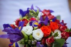 婚姻的装饰花束上升了与两个金黄圆环 免版税库存照片