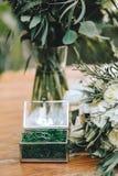 婚姻的金戒指的一个美丽的jewerly玻璃箱子与青苔 在一个在w的新娘和玉树的花束附近有白花的 免版税库存照片