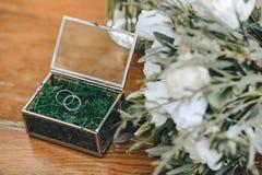 婚姻的金戒指的一个美丽的jewerly玻璃箱子与青苔 在一个新娘的花束附近有白花的在一木backgroun 免版税库存图片