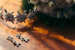 婚姻花束白玫瑰阳光地板Compocition关闭的银色长的耳环金刚石头发箍钢花  库存照片