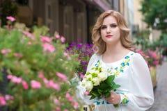 婚姻,有摆在花篱芭附近的婚礼花束的美丽的女孩在利沃夫州 库存照片