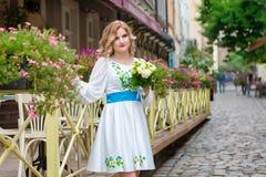 婚姻,有摆在花篱芭附近的婚礼花束的美丽的女孩在利沃夫州 免版税库存图片