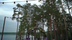 婚姻 新娘仪式花婚礼 成拱形,用站立在森林的紫罗兰色和黄色花装饰,婚礼的 股票视频