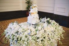 婚宴喜饼和白花在桌上的瓣装饰 免版税图库摄影