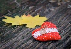 婚戒、叶子和心脏在木背景 免版税库存图片