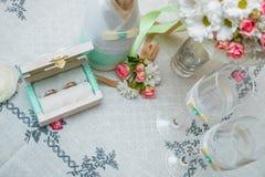 婚戒、新娘的花束在瓶香槟附近和两个葡萄酒杯在白色桌布 顶视图 免版税库存图片