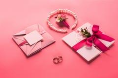 婚戒、珍珠项链、钮扣眼上插的花和桃红色信封与邀请 免版税库存照片