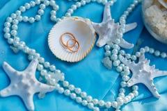 婚戒、船舶题材、海星和珍珠 免版税库存照片