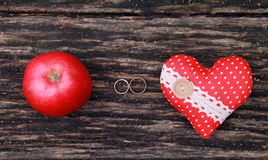 婚戒、苹果和心脏在木背景 免版税库存图片