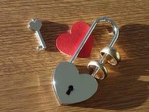 婚戒、钥匙、锁和红色心脏 免版税库存图片