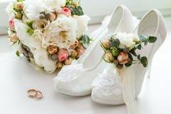 婚戒、钮扣眼上插的花、花束和女傧相鞋子 图库摄影