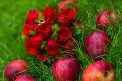 婚戒与猩红色玫瑰的onl花束 库存图片