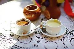 婚戒和两个杯子热的白色和牛奶巧克力在一张白色鞋带桌布,点心,甜点, dcor,咖啡馆,匙子 免版税库存图片
