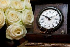 婚戒和古色古香的时钟 库存图片