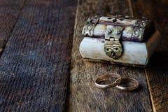 婚戒和小箱在一张木桌上 库存图片