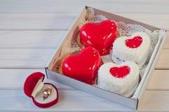 婚戒和心脏在箱子的形状蛋糕在桌上 免版税库存图片