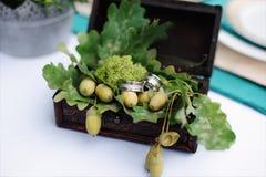 婚戒和橡木叶子在箱子 免版税库存照片