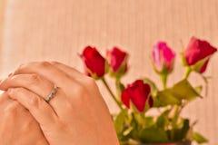 婚戒在妇女手上有红色和桃红色玫瑰背景 免版税库存图片