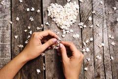 婚戒在手和花背景的白色心脏 免版税库存照片