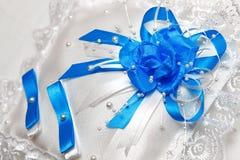婚戒的枕头与蓝色丝带 免版税库存照片