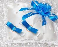 婚戒蓝色丝带的白色枕头 库存图片