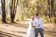 结婚的婚姻的夫妇画象  愉快的新娘,站立在海滩的新郎,亲吻,微笑,笑,获得乐趣在秋天pa 免版税库存图片