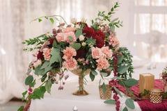 婚礼与红色和桃红色花的桌装饰在白色布料 免版税库存图片