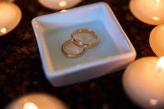 婚礼与蜡烛的钻戒在水中 免版税库存图片
