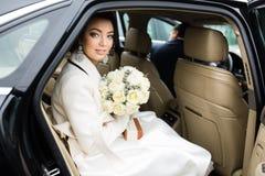 婚礼之日:有白花花束的美丽的新娘在汽车的 免版税图库摄影