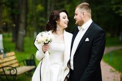 婚礼之日:美丽的新娘和新郎在公园 图库摄影