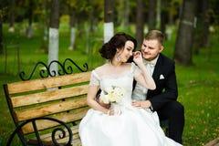 婚礼之日:美丽的新娘和新郎坐长凳在公园 库存图片