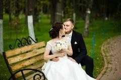 婚礼之日:美丽的新娘和新郎坐长凳在公园 免版税库存图片
