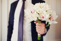 婚礼兰花花束在新郎的手上 库存图片