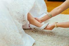 婚礼准备 新娘的女朋友在我的鞋子婚姻帮助她 库存照片
