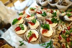 婚礼品种夏天点心用新鲜水果和莓果在用打好的奶油与鲜美自助餐颜色装饰的蛋糕,糖果 图库摄影