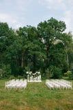 婚礼在一个美丽的庭院里 白色椅子和被反映的桌 有花水芋百合孤挺花的玻璃花瓶 库存图片