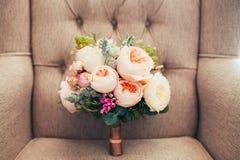 婚礼在一把典雅的扶手椅子的牡丹花束 免版税库存图片