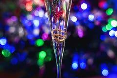 婚礼在一杯的金戒指在一明亮五颜六色的香槟 库存照片