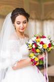 婚礼在婚礼之日开花,拿着五颜六色的花束用她的手的妇女 图库摄影