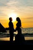 婚礼在握手的海滩的夫妇剪影 免版税库存图片