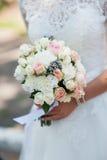 婚礼在新娘手上开花玫瑰花束有在背景的白色礼服的 免版税图库摄影