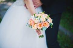 婚礼在新娘手上开花玫瑰花束有在背景的白色礼服的 免版税库存图片