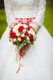 婚礼在新娘手上开花玫瑰花束有在背景的白色礼服的 库存照片