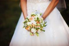 婚礼在新娘手上开花玫瑰花束有在背景的白色礼服的 免版税库存照片