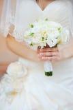 婚礼在新娘手上开花花束有在背景的白色礼服的 免版税库存照片